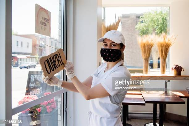 owner opening her store with protective mesure againts covid-19. - retail place stock pictures, royalty-free photos & images
