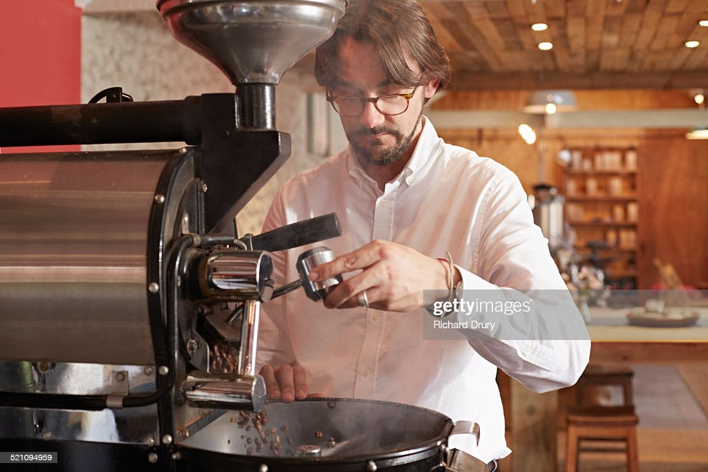 Owner operating in coffee roaster : Stock Photo