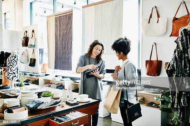 owner processing credit card with digital tablet - hi tech moda stock pictures, royalty-free photos & images