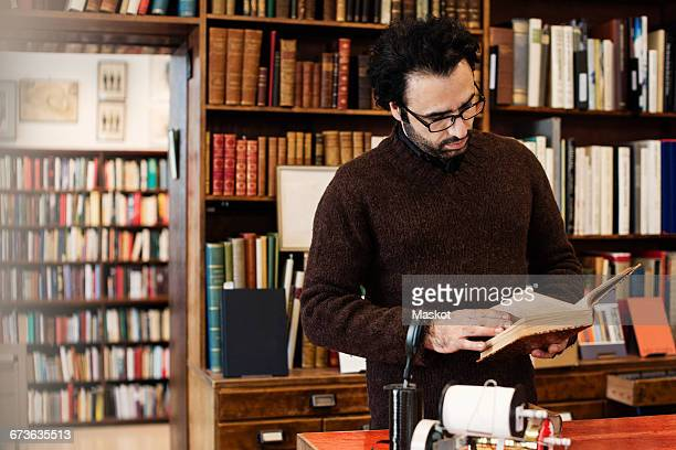 Owner reading book while standing in store