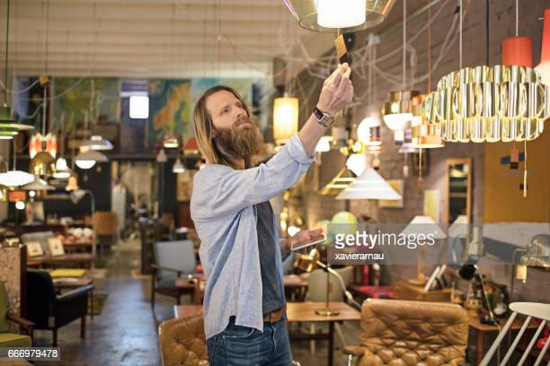 Owner reading tag on lighting equipment in store
