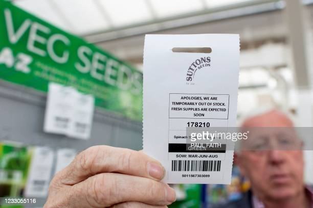 Owner Robin Mercer holds up an 'out of stock' notice as he poses near packets of seeds at Hillmount Garden Centre in east Belfast on May 19 where...