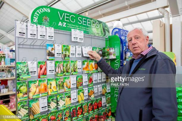 Owner Robin Mercer points out a 'out of stock' notice as he poses with packets of seeds at Hillmount Garden Centre in east Belfast on May 19 where...