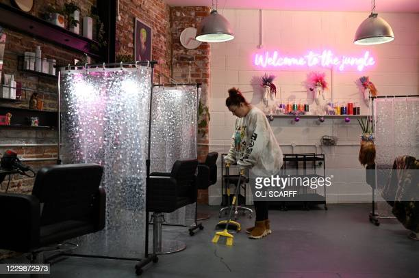 Owner Sarah Clayton poses for a photograph as she readies her Mousey Brown's hair and beauty salon for opening again, in Hull, in north-east England...
