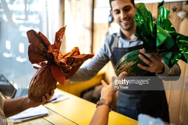 店内でイースターエッグを販売するオーナー - イースターエッグのチョコレート ストックフォトと画像