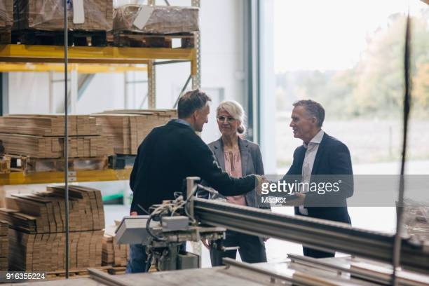 owner shaking hands with businessman standing by colleague in lumber industry - construction material stock pictures, royalty-free photos & images