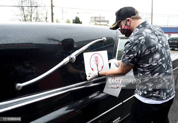 Owner Shon Boulden applies a sticker to the side of the hearse that is being used to make deliveries for the Lucky Devil as they prepare to go out on...