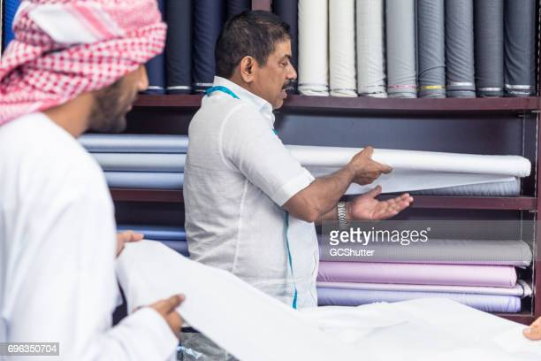 Owner showing his middle eastern customer several fabric swatches