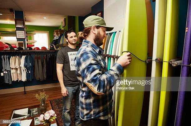 Owner shows boards to customer at a surf shop.
