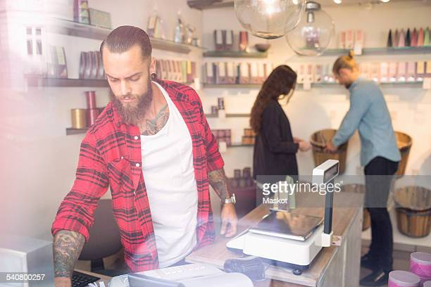 Owner standing at checkout counter while customers shopping in background