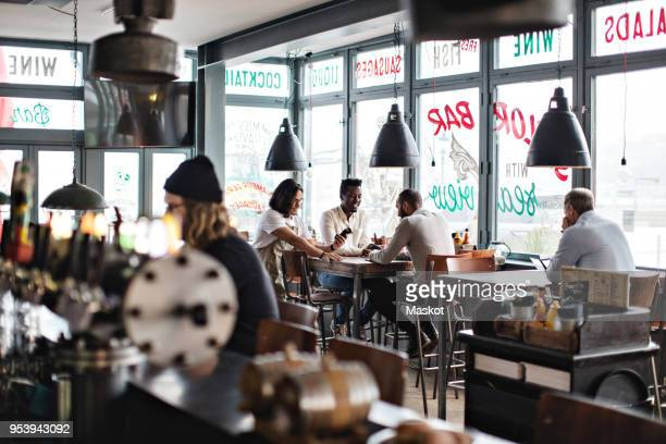 Owner standing by young customers at table in restaurant