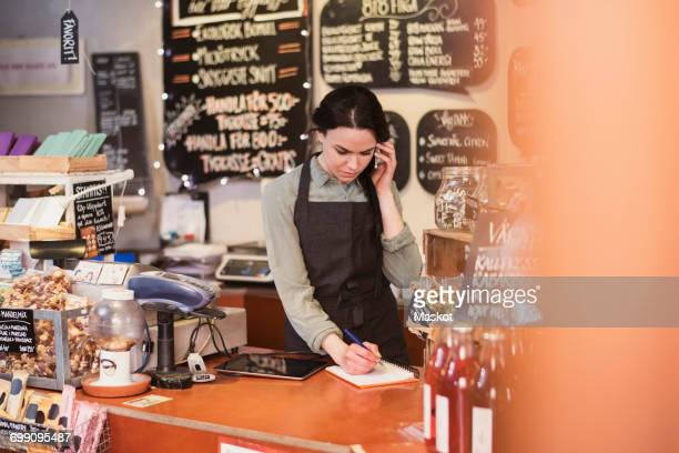 Owner talking on phone while writing on note pad at checkout counter in store