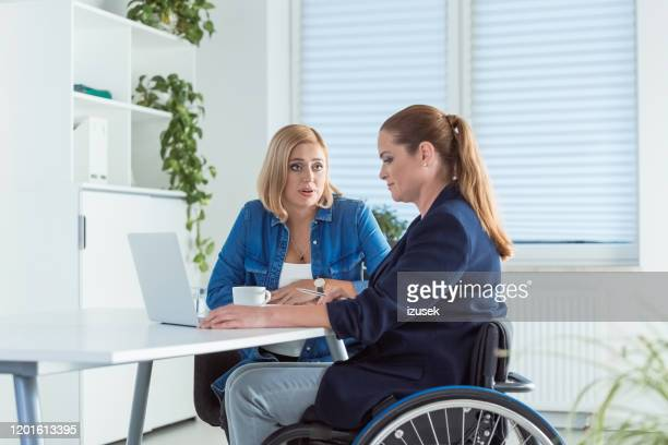 owner talking to disable coworker on wheelchair - persons with disabilities stock pictures, royalty-free photos & images