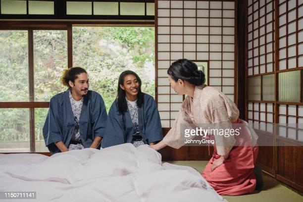 伝統的な旅館の宿泊客に話しかけているオーナー - 観光客 ストックフォトと画像