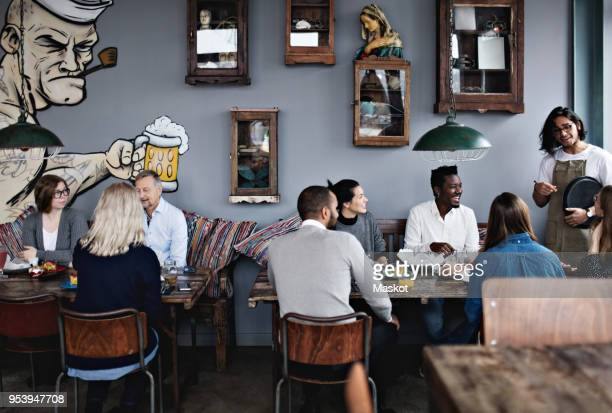 Owner talking to multi-ethnic friends while family having brunch at table in restaurant