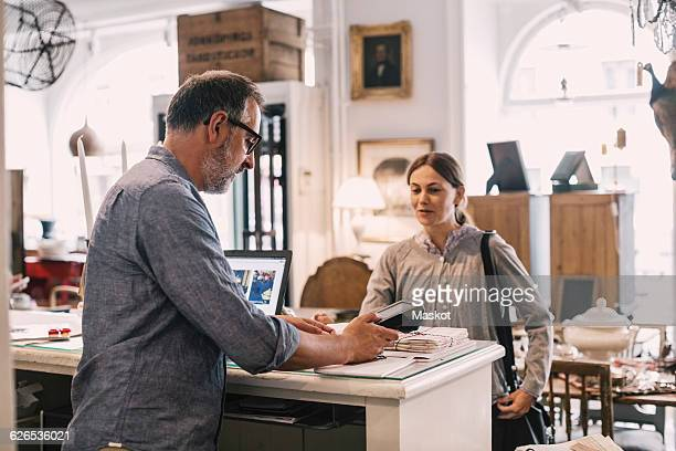 Owner using card reader in front of female customer at shop counter