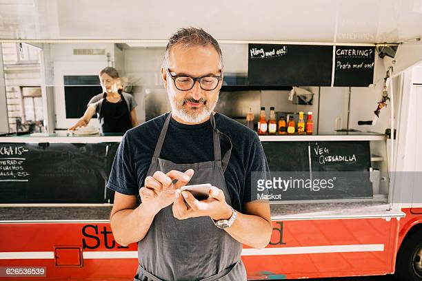 Owner using mobile phone against street food truck