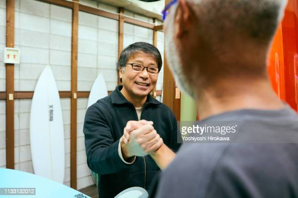 owner who shakes hands with customers on smile in shop - honesty stock pictures, royalty-free photos & images