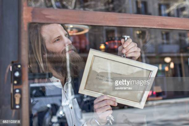 owner with open sign at furniture store window - store opening stock pictures, royalty-free photos & images