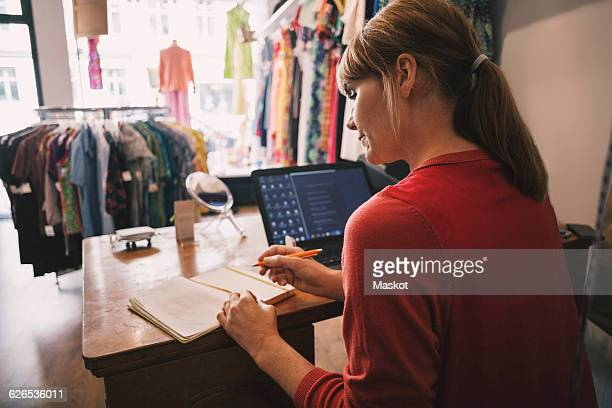Owner working while sitting at desk in thrift store