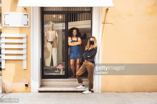 proprietari in una boutique per piccole imprese in posa sulla porta d'ingresso - opening event foto e immagini stock