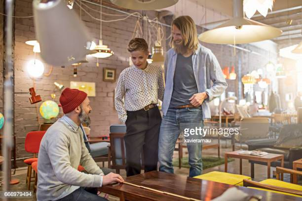 Owners measuring wooden table at illuminated store