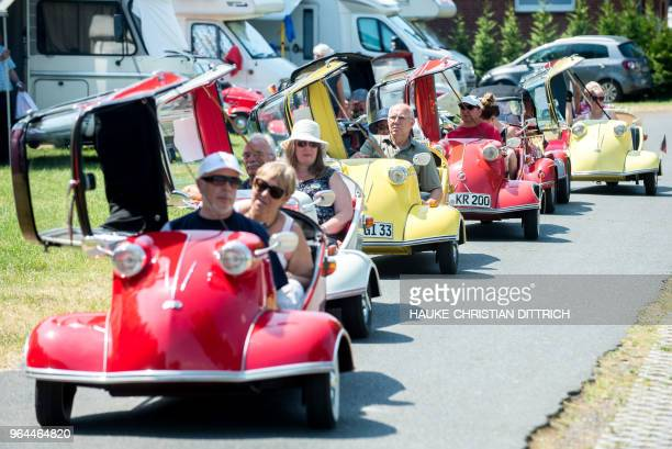 Owners of Messerschmitt Kabinenroller vintage microcars drive across a camping site during the annual meeting of the MesserschmittClub in Uetze near...
