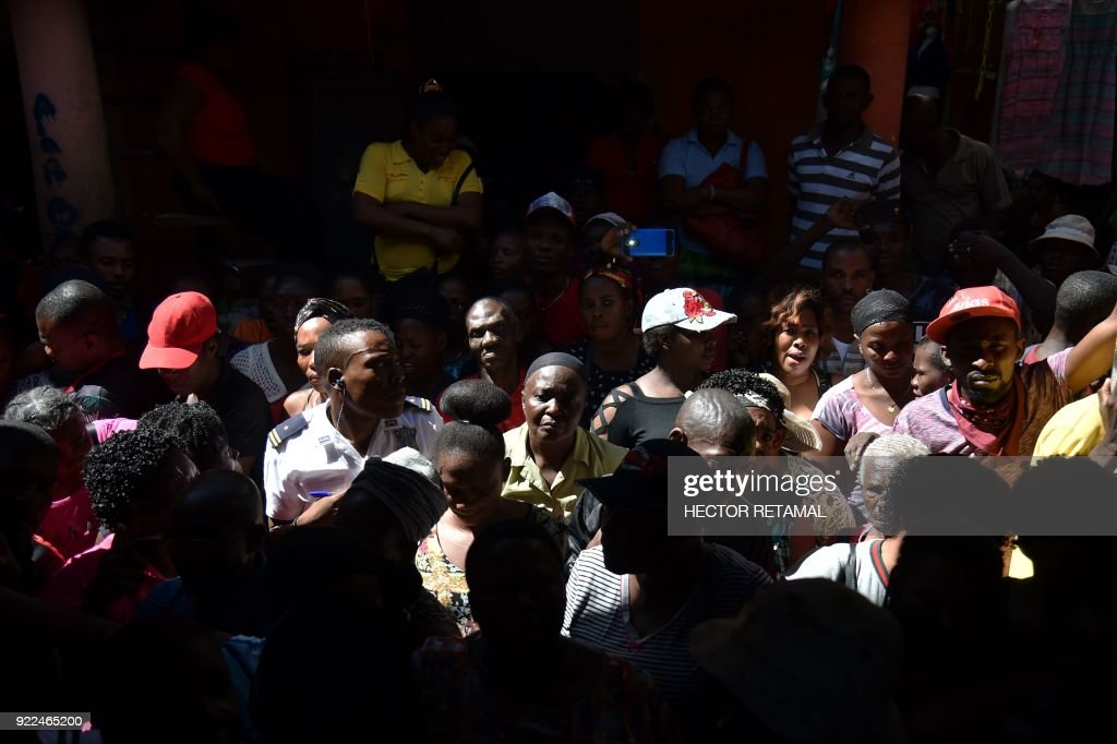 Owners of shops wait while authorities visiting the Shop owners wait as authorities inspect the worse-hit area at the Nan Gerit Market in Port-au-Prince on February 21, 2018. A fire gutted the textiles market in Haiti's capital on February 18. /