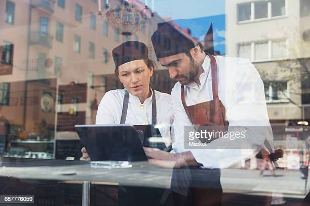 Owners using digital tablet in grocery store seen through glass window