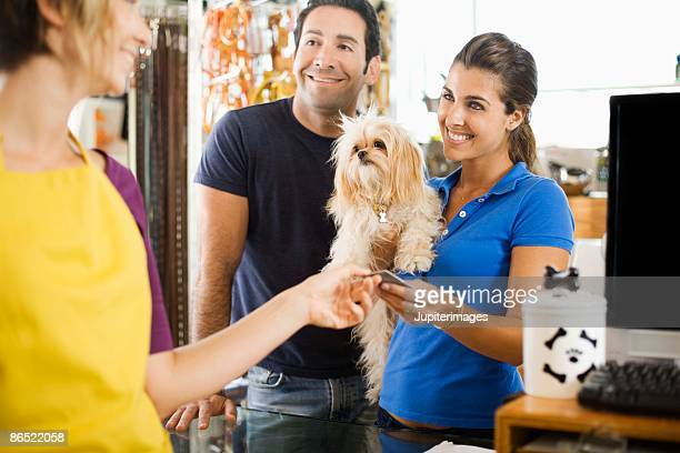 Owners with dog paying groomer