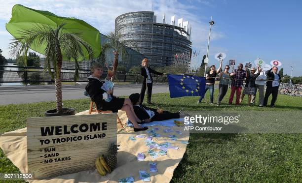 Oxfam activists hold placards during a demonstration against tax evasion in front of the European Parliament on July 4 2017 in Strasbourg eastern...
