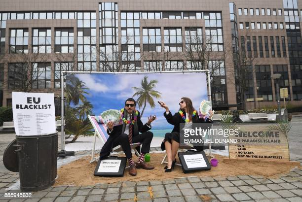 Oxfam activists stage a satirical streetplay mimicking wealthy people hidding their money in tax haven on December 5 2017 near the European...