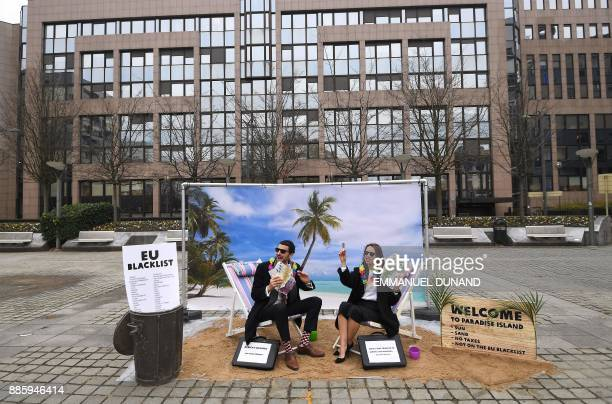 TOPSHOT Oxfam activists stage a satirical streetplay mimicking wealthy people hidding their money in tax haven on December 5 2017 near the European...
