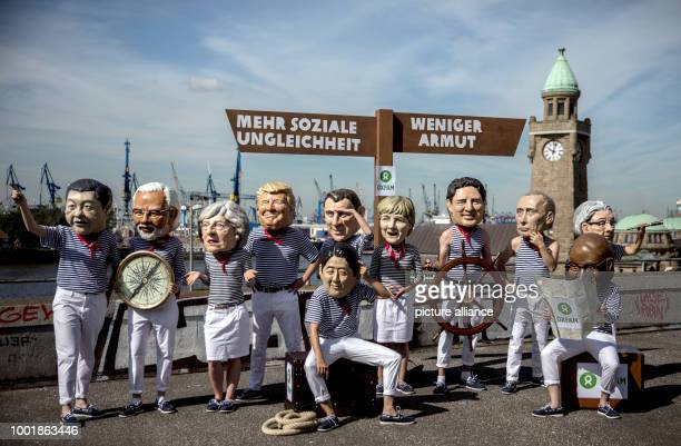 Oxfam activists wear masks of the heads of government during a demonstration involving a splitting road sign reading 'Mehr soziale Ungleichheit' and...