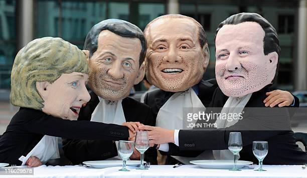 Oxfam activists wearing masks depicting German Chancellor Angela Merkel French President Nicolas Sarkozy Italy's Prime Minister Silvio Berlusconi and...