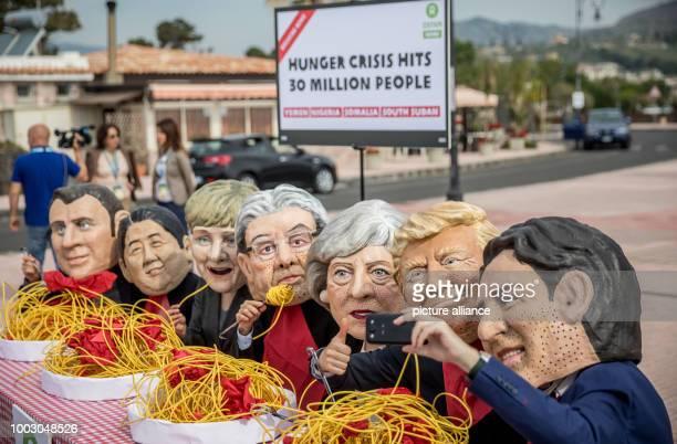 Oxfam activists wearing masks of the G7heads of French President EmmanuelMacron Japan's Prime Minister Shinzo Abe German's Chancellor Angela Merkel...