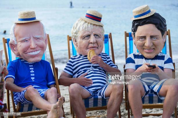 Oxfam campaigners pose as G7 leaders as the charity calls on the G7 to commit to cutting emissions further and faster on June 12, 2021 in Swanpool...