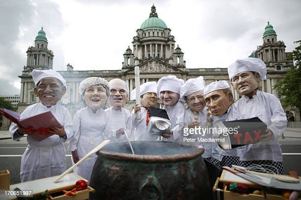 Oxfam charity volunteers wear masks depicting the G8 leaders during a photocall outside City Hall on June 16 2013 in Belfast Northern Ireland The G8...