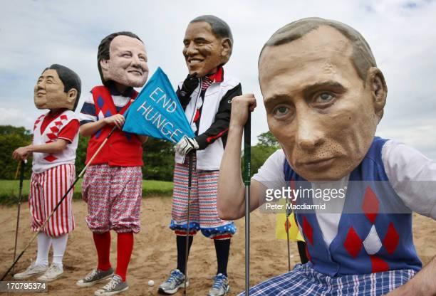 Oxfam volunteers wearing caricature heads depicting Japanese Prime Minister Shinzo Abe British Prime Minister David Cameron US President Barack Obama...