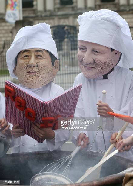 Oxfam workers wear masks depicting Japanese Prime Minister Shinzo Abe and Britain's Prime Minister David Cameron during a photocall on June 16 2013...