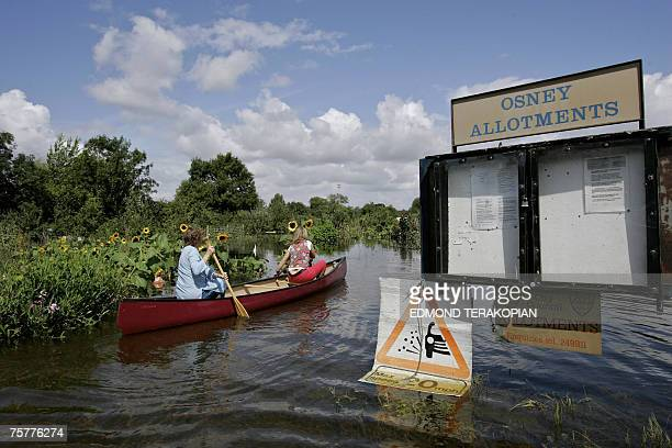 Bev Lear and Kate Stewart inspect their flooded out allotment plots at the Osney Allotments in Oxford July 27 2007 after the River Thames burst its...