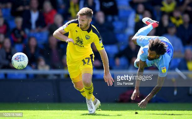 Oxford United player James Henry is challenged by Coventry City player Junior Brown during the Sky Bet League One match between Oxford United and...