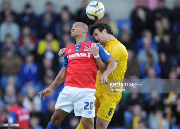 Oxford United's Jake Wright and Gillingham's Deon Burton battle for the ball during the npower Football League Two match at the Kassam Stadium Oxford