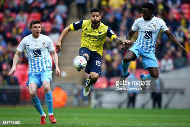 Oxford's Kane Hemmings battles for the ball in the air with Coventry's Gael Bigirimana during the EFL Checkatrade Trophy Final between Coventry City...