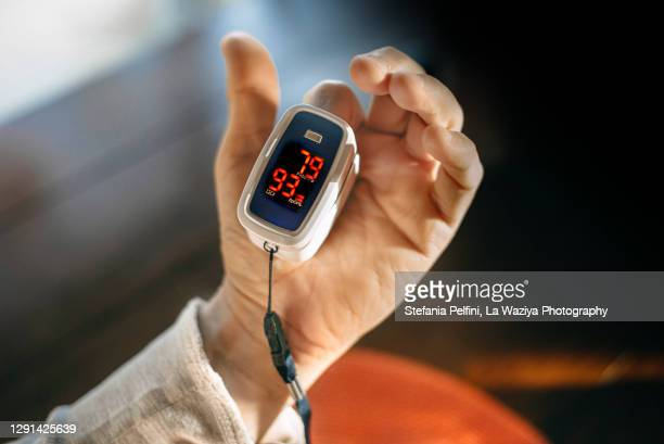 oximeter for checking oxygen saturation in blood on male hand - pulse oximeter stock pictures, royalty-free photos & images