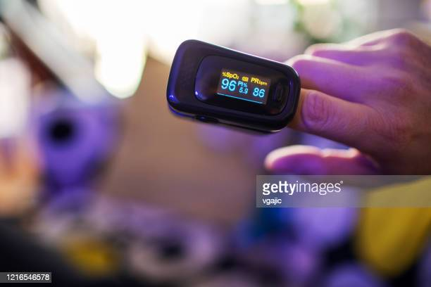 covid-19 oximeter for checking oxygen saturation in blood - pulse oximeter stock pictures, royalty-free photos & images