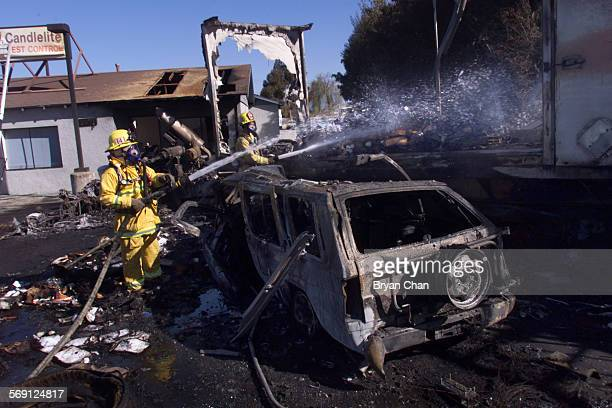 Oxnard firefighters hose off the remains of FedEx tractor trailor that hit a flatbed truck veered off northbound Highway 101 hit several parked cars...