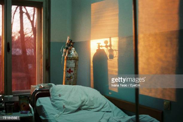 Oxygen Tank By Bed Against Window In Hospital During Sunset