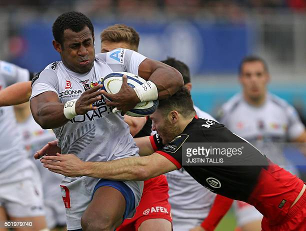 Oyonnax's centre from Fiji Uwanakaro Tawalo is tackled by Saracens' centre from Scotland Duncan Taylor during the European Rugby Champions Cup rugby...