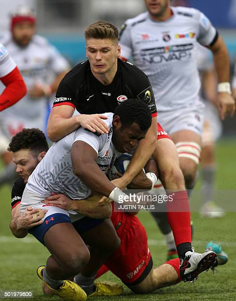 Oyonnax's centre from Fiji Uwanakaro Tawalo is tackled by Saracens' centre from Scotland Duncan Taylor and Saracens' fly-half from England Owen...